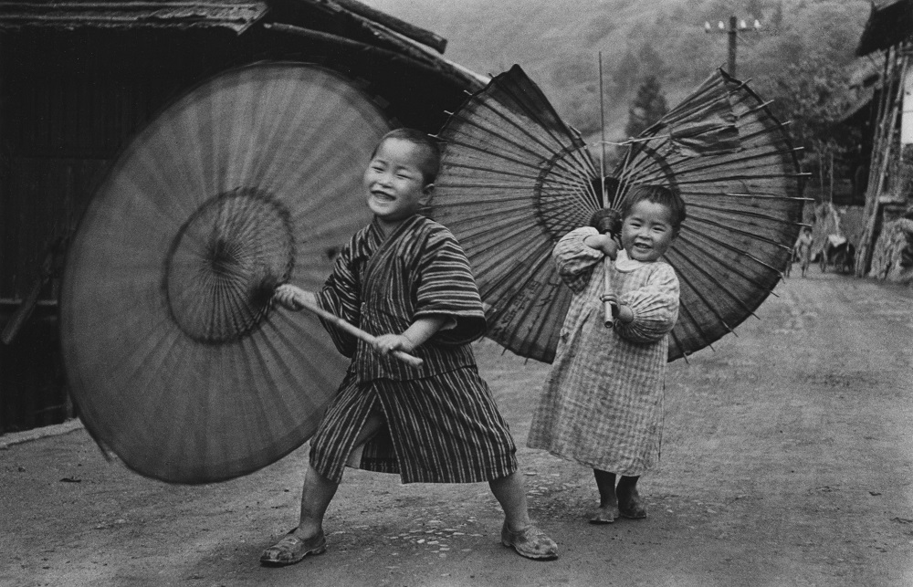 Domon Ken, Bambini che fanno roteare gli ombrelli, 1937 circa, dalla serie Bambini (Kodomotachi), Ogōchimura. Ken Domon Museum of Photography
